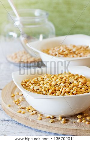Dry peas in a ceramic bowl on a white wooden table. Bio healthy food. Selective focus