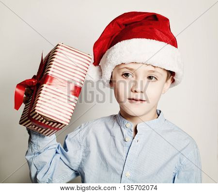 What is in the Christmas Box? Child with Christmas Gift and Santa Hat