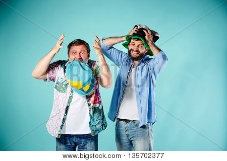 The two football fans with different emotions over blue background
