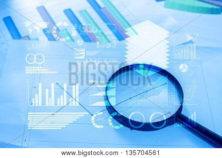 Magnifying glass and documents with analytics data lying on tableselective focus