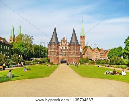 Luebeck Germany - May 23 2008: Holstentor famous landmark of the city park with people on meadow in front.