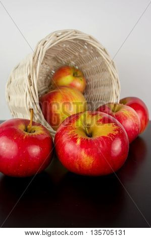 Fresh harvest of apples. Nature theme with red grapes and basket on wooden background. Nature fruit concept.