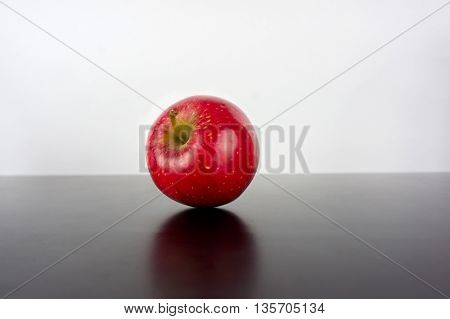 Red apple on a black background with reflection / Red apple on a black background