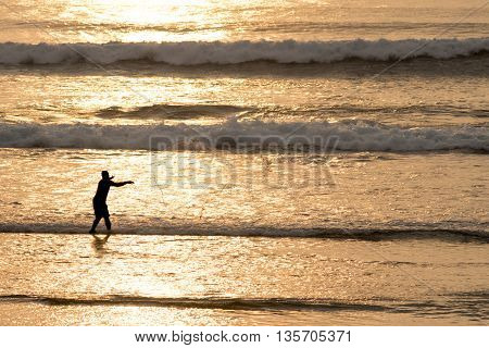 Silhouette Of Man With Fish Net On Beach Water