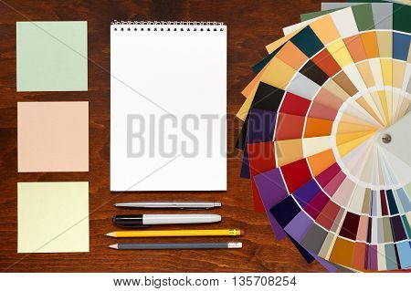 Designer working place Color palette guide on the wooden background and notepad. mockup template