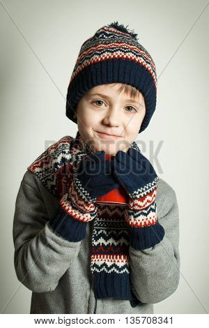 Happy child wearing a woolen hat and scarf drinking hot tea