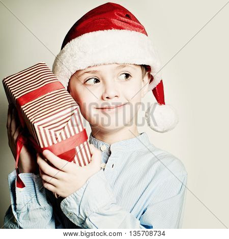 Christmas Child holdind Gift. Happy Little Boy with Santa Hat and Xmas Box
