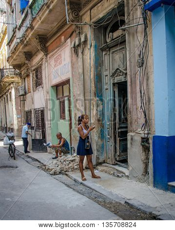 HAVANA - CUBA JUNE 19, 2016: A young woman checks her cell phone for messages outside her home, one of thousands of deteriorating and decaying buildings in La Habana Vieja.