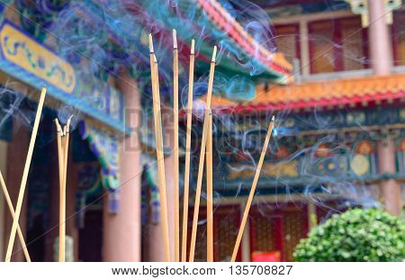 Selective focus on front of jossticks, Incense sticks are burning with smoke use for pay respect to the Buddha