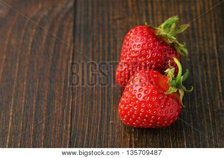 Fresh tasty strawberries on old wooden background