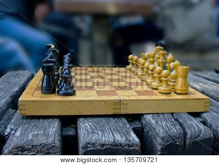 chess game on an old wooden bench