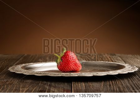 tasty red strawberry on a vintage plate