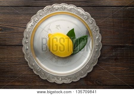 Fresh lemon with leaves on a vintage plate top view