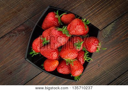 Strawberries in black plate. wooden background top view