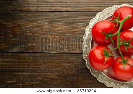 tomatoes on vintage plate top view, wooden background