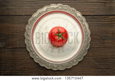 tomato on vintage plate top view, wooden background