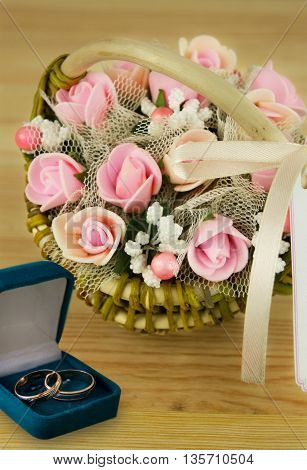 a bouquet of flowers in a basket of handmade wedding rings