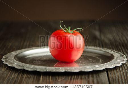tomato on vintage plate front view, wooden background