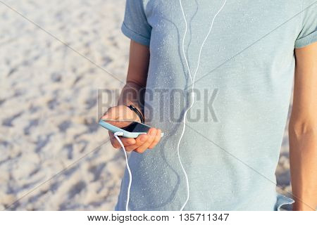 Close-up Of A Girl In A Blue T-shirt Holding A Mobile Phone In Hand And Listening To Music With Head