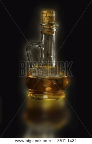 glass carafe with oil on a black background