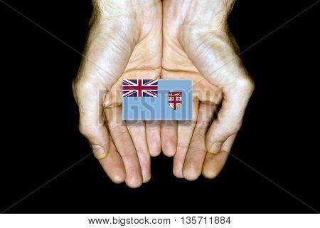 Flag Of Fiji In Hands On Black Background