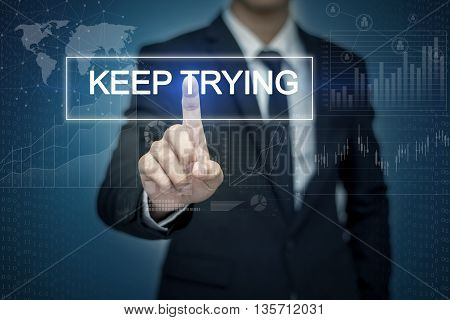 Businessman hand touching KEEP TRYING button on virtual screen