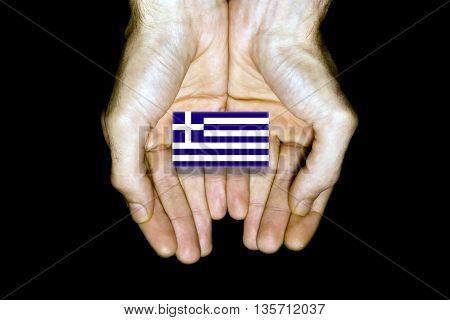 Flag Of Greece In Hands On Black Background