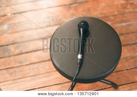 the singer left a wired microphone lying on a round black chair