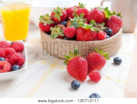 still life of strawberries with cup of coffee and glass of juice