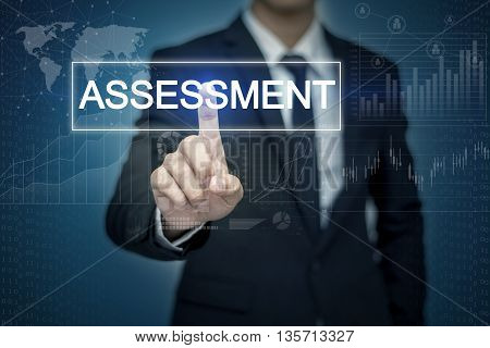 Businessman hand touching ASSESSMENT button on virtual screen