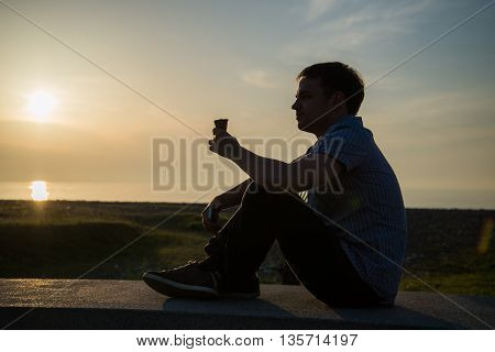 Young man at promenade eating an ice-cream and using his phone, maybe he is single or waiting for someone.