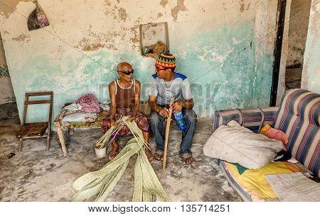 Mobmasa, Kenya- March 16,2016: Old blind African man making leaf artwork out of dry banana leaf