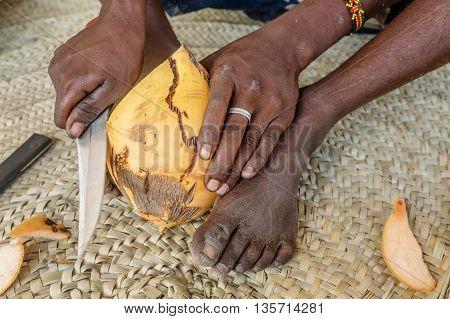 African man cutting coconut in Kenya Africa