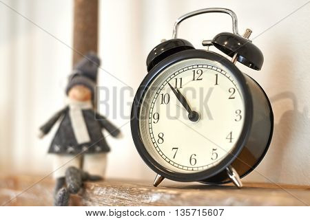 The old alarm clock on wooden shelf