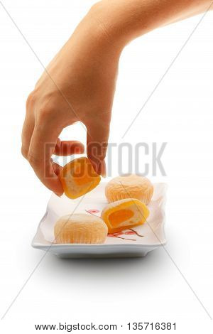 Beautiful elegant female hand taking mango mochi dessert from white square ceramic plate with japanese rice cakes isolated on white background.