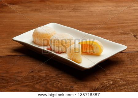 Beautiful mango mochi rice cakes in a cut on white square ceramic plate standing on brown wooden table.