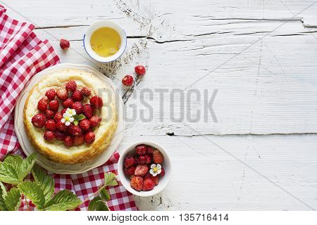 Simple homemade cheesecake with strawberry liquid with floral honey in the honey comb on a simple wooden background.