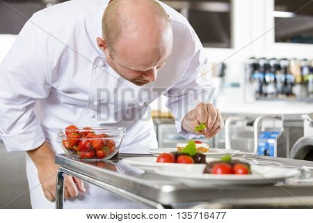 Close-up of a professional male chef who decorates dessert cake with strawberry and lemon leaf. Large industry kitchen.