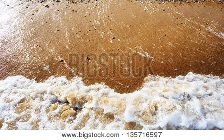 Sea wave on orange pebble sand beach. Abstract background with copy space.