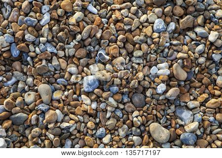 A close-up of the pebbled beach along the Hastings Seafront in Sussex.
