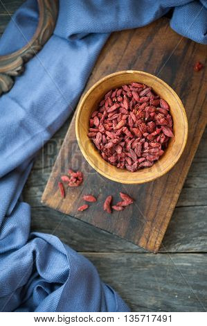 Dry goji berry in a wooden bowl on a rustic background