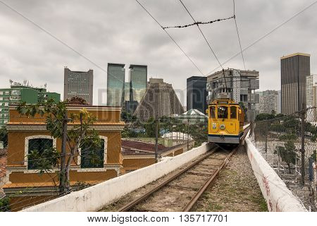 Rio de Janeiro, Brazil - June 18, 2016: The new version of iconic bonde tram is passing on the top of the Arch of Lapa, which was once an aqueduct.
