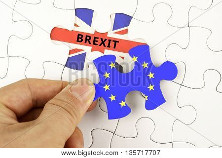 Hand Holding Piece Of Jigsaw Puzzle With The Flag Of European Union And Word Brexit On Great Britain