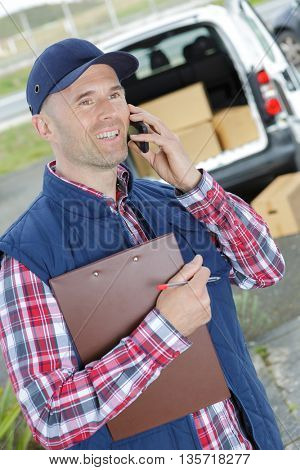 male worker in front truck using mobile phone