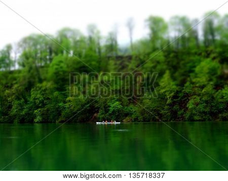 Four people on a canoe in a green environment. Blurred to create a miniature view of the canoe on the tranquil Rhine river. the water is emerald green and reflects the vegetation.