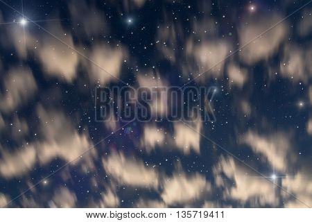 Beautiful abstract heavenly background with blurred clouds in the form of nebulae and stars on the background of the blue sky taken with a long exposure
