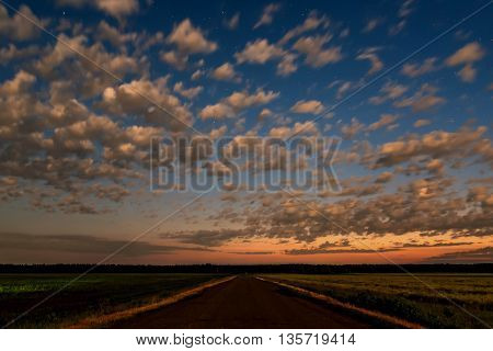 Scenic evening landscape with the road among fields on a background of blue sky with beautiful clouds and stars at sunset taken with a long exposure