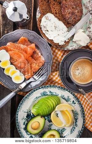 Breakfast With Salmon, Eggs, Avocado, Bread, Cheese And Coffee