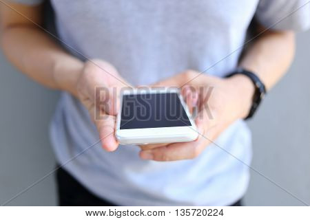 Man holding and use white color smartphone