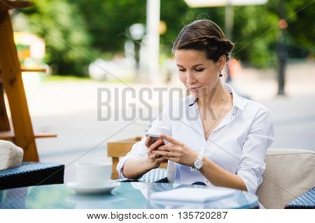 Portrait of a charming business woman chatting on her smart phone while waiting someone in cafe outdoors, gorgeous female using mobile phone while sitting in cozy restaurant in the fresh air during lunch.